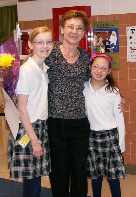 Mrs. Schneider is pictured here with Holy Cross students, daughter Maddie Schneider and Bella DeBrevi.